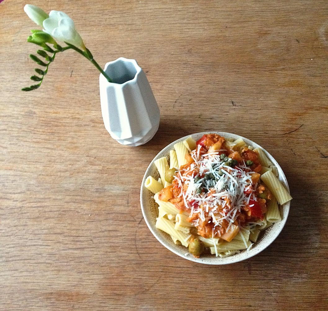 Pasta with lentil-sauce and vase with white flower on a table.