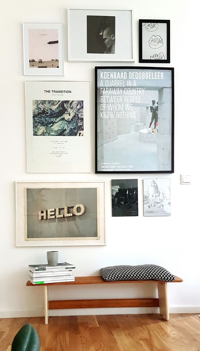 Art posters in frames of different shape and size on a white wall combined to a gallery wall.