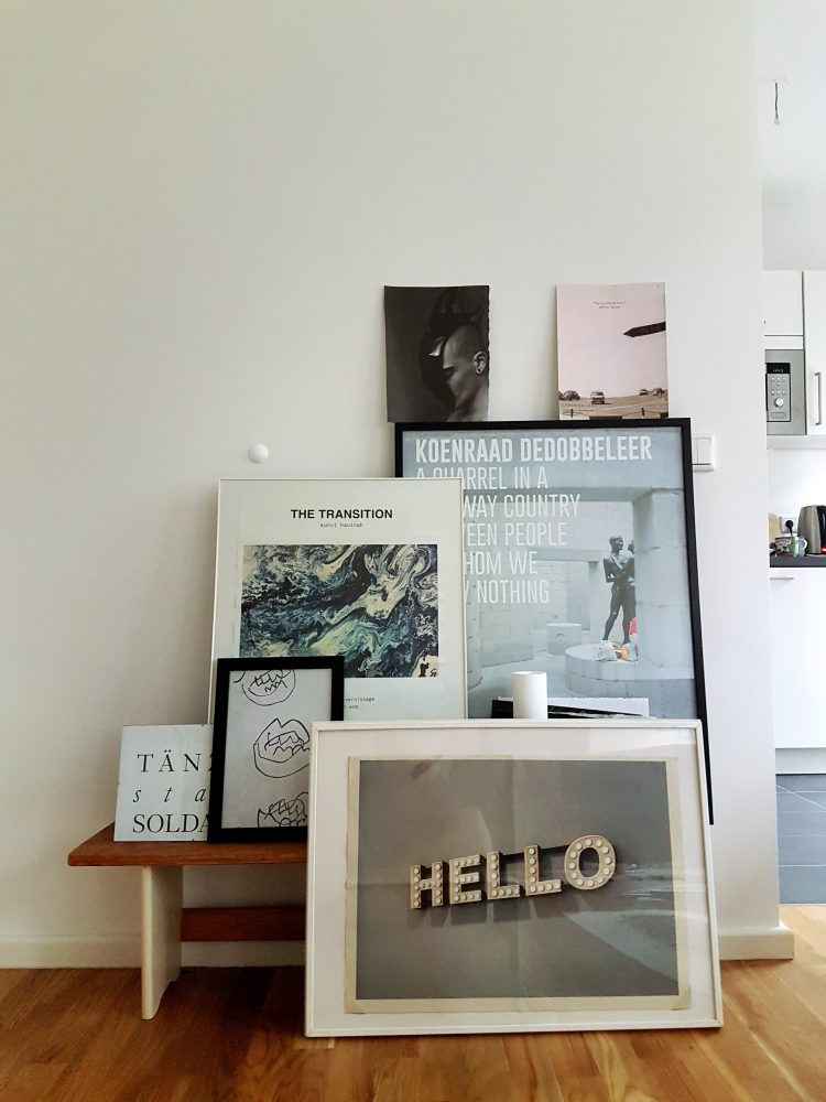Art posters and photographs in different frames combined to a gallery wall.