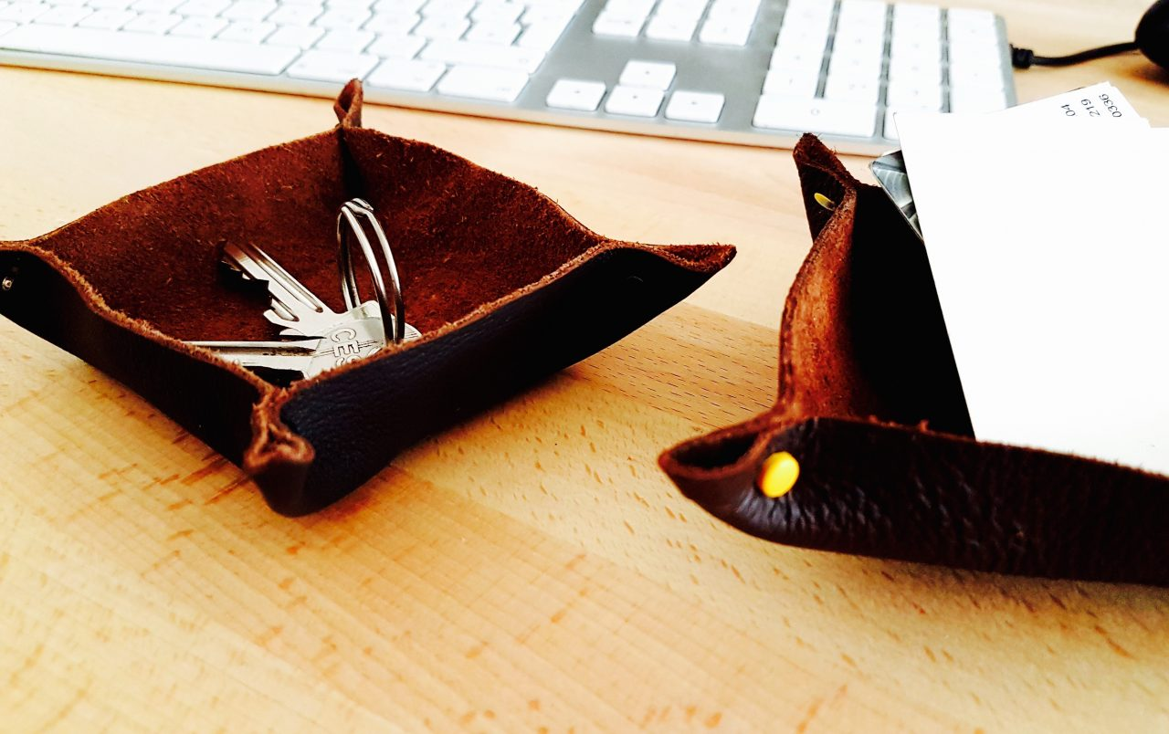 Two brown leather key dishes on a desk