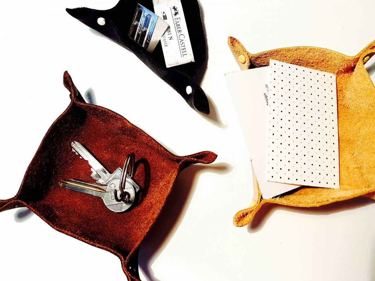 Three handmade leather key dishes in different shapes and colors
