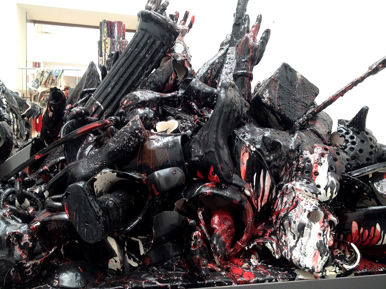 A sculpture made of a huge pile of different objects painted in black and red.
